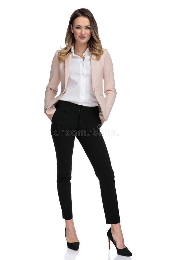 Mulher de negócios atrativa em suportes do terno e em uns bolsos cor-de-rosa da posse foto de stock royalty free