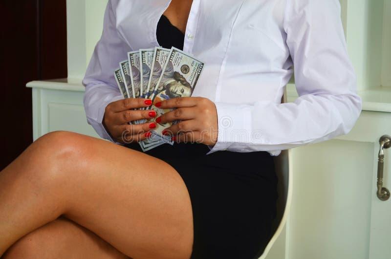 A mulher de negócios atrativa está guardando o dinheiro em suas mãos fotografia de stock royalty free