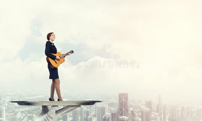 Mulher de negócios atrativa na bandeja do metal que joga a guitarra acústica contra o fundo da arquitetura da cidade foto de stock royalty free