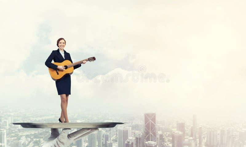 Mulher de negócios atrativa na bandeja do metal que joga a guitarra acústica contra o fundo da arquitetura da cidade imagens de stock royalty free