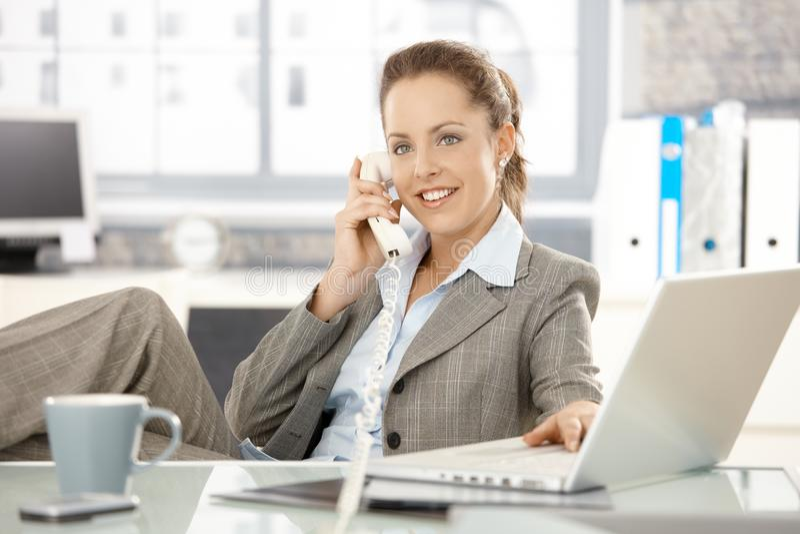 Mulher de negócios atrativa que fala no sorriso do telefone foto de stock