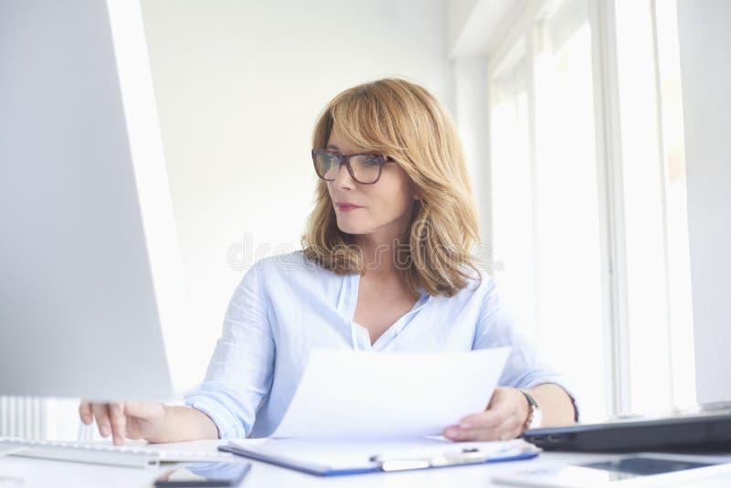 Mulher de negócios atrativa que trabalha no computador no escritório foto de stock royalty free