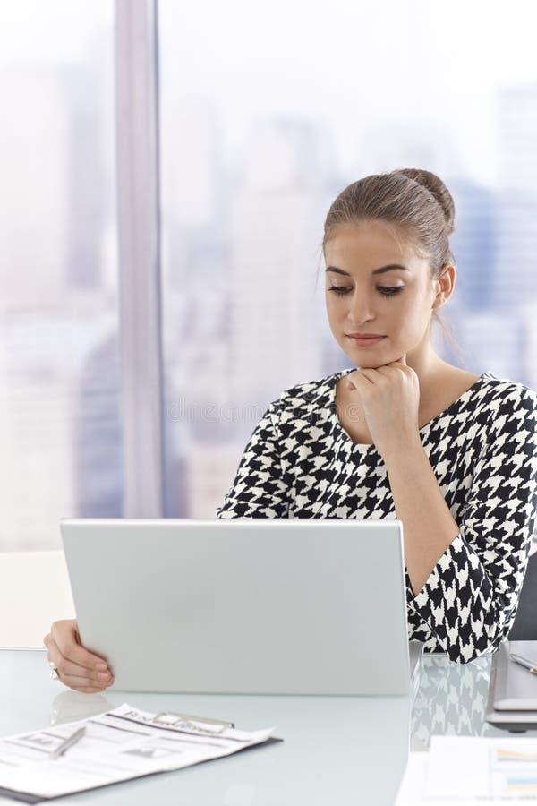 Mulher de negócios atrativa que usa o computador portátil foto de stock