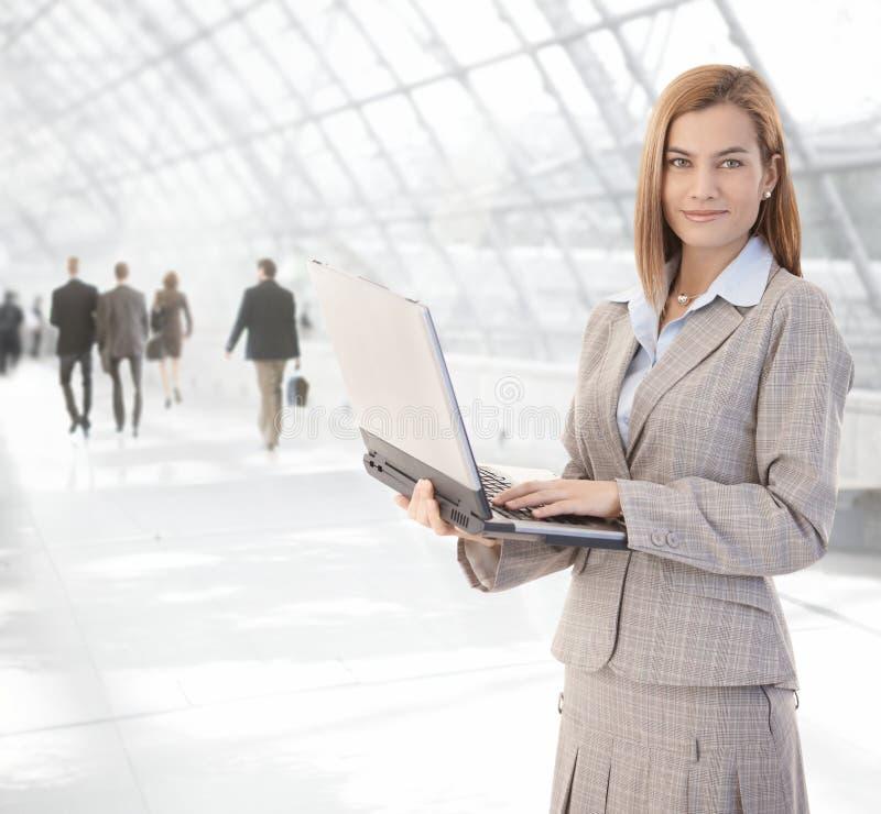 Mulher de negócios atrativa que usa o portátil na passagem fotografia de stock