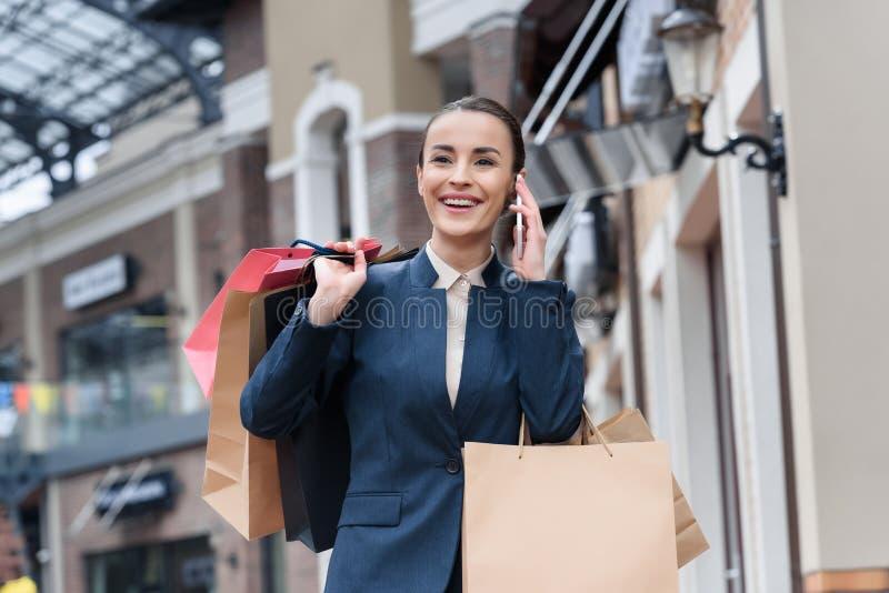 mulher de negócios atrativa de riso que fala o smartphone e guardar fotografia de stock royalty free