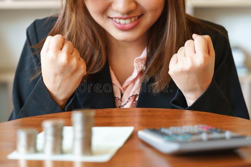 A mulher de negócios bem sucedida com moedas e o livro de conta depositam cortejam sobre foto de stock royalty free