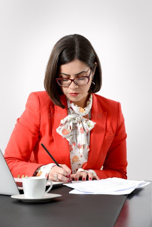 Mulher de negócios bem sucedida nova que assina um original fotos de stock