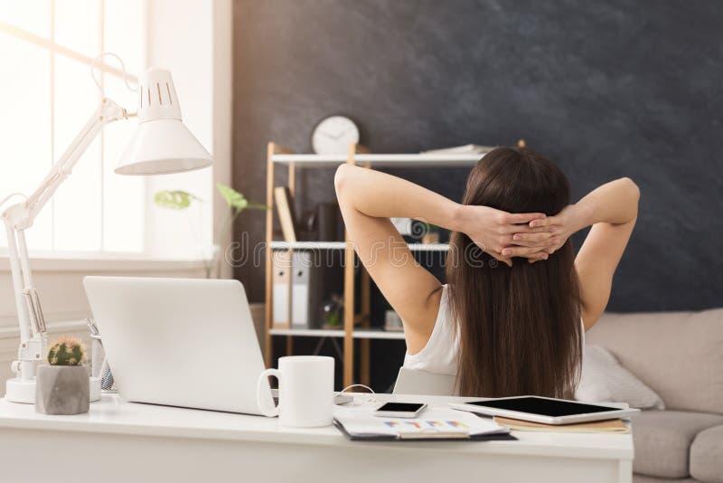 Mulher de negócios bem sucedida que descansa com mãos atrás de sua cabeça fotos de stock