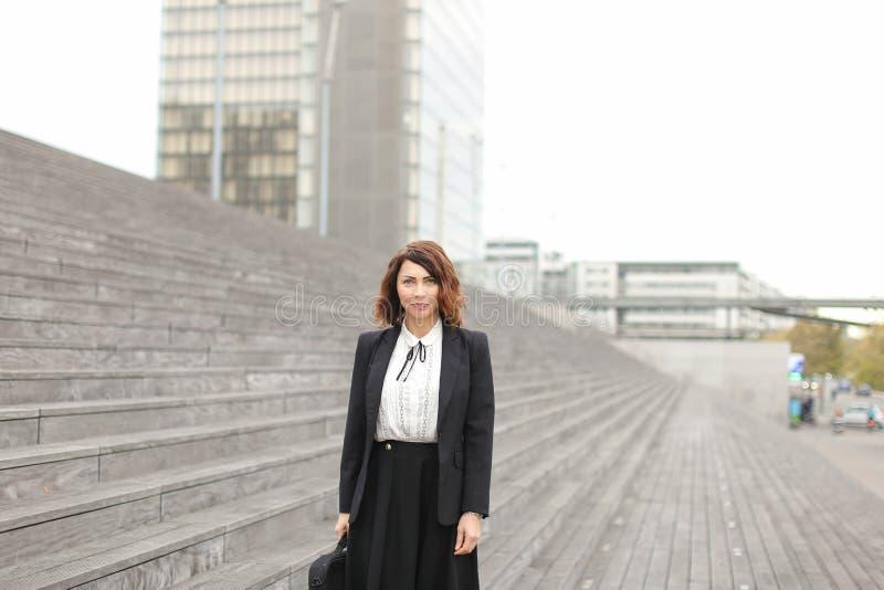 Mulher de negócios bem sucedida que está em escadas com saco e em construções altas no fundo fotografia de stock royalty free