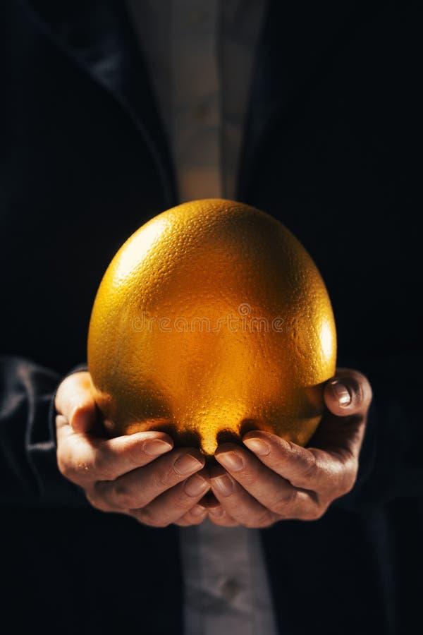 Mulher de neg?cios bem sucedida que guarda o ovo dourado foto de stock