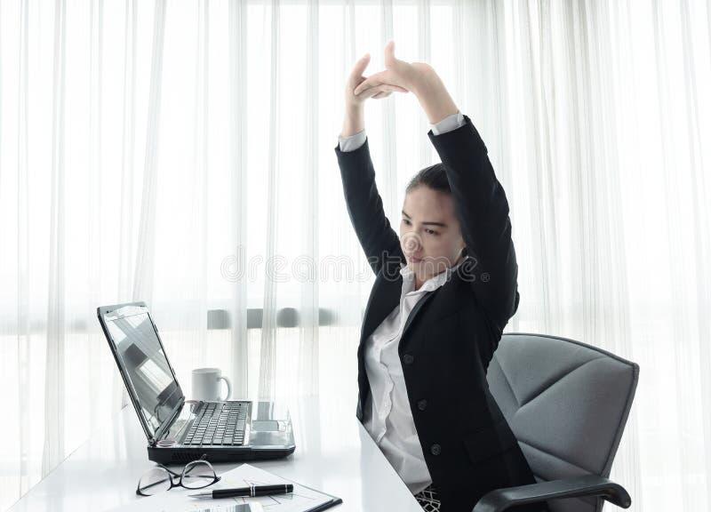 Mulher de negócios bem sucedida que relaxa em sua cadeira no escritório imagens de stock royalty free