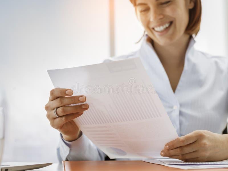 Mulher de negócios bem sucedida que verifica relatórios financeiros imagem de stock royalty free