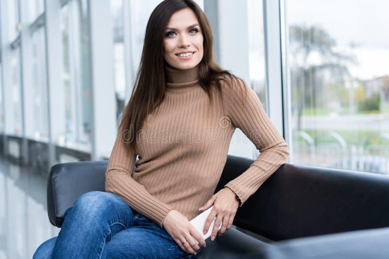 Mulher de negócios bonita alegre que senta-se na poltrona no escritório e que olha afastado fotos de stock
