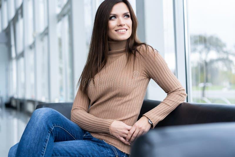 Mulher de negócios bonita alegre que senta-se na poltrona no escritório e que olha afastado foto de stock