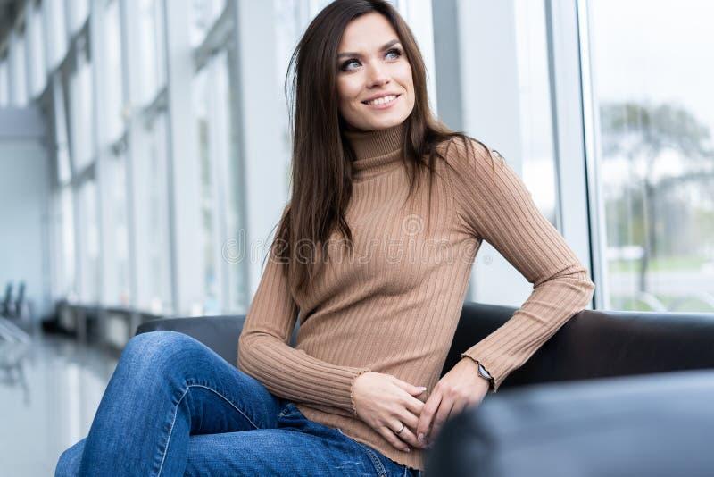 Mulher de negócios bonita alegre que senta-se na poltrona no escritório e que olha afastado imagens de stock royalty free