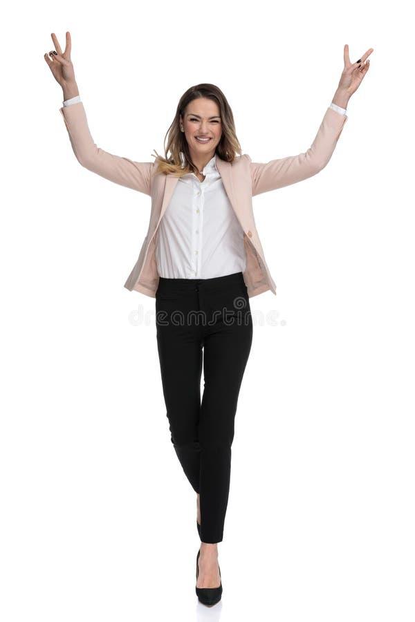 A mulher de negócios bonita anda e comemora com mãos no ar imagens de stock royalty free