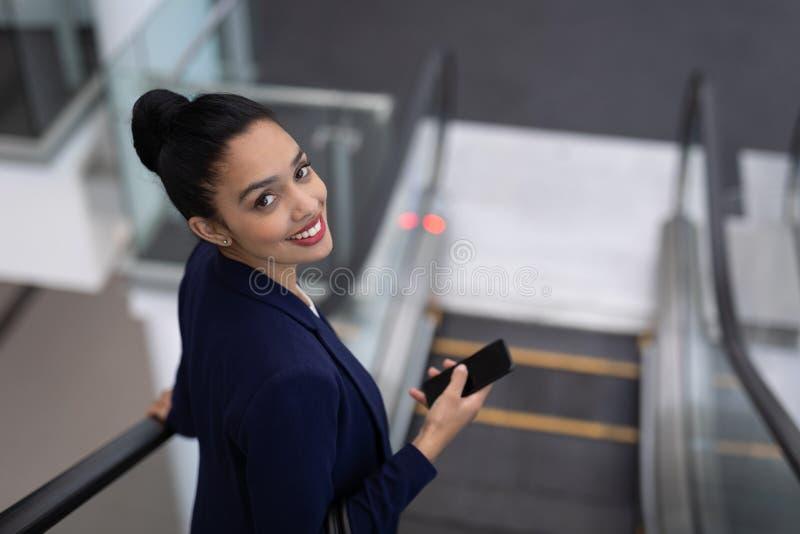 Mulher de negócios bonita da misturado-raça com o telefone celular que olha a câmera na escada rolante no escritório moderno fotografia de stock royalty free