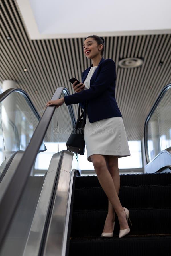 Mulher de negócios bonita da misturado-raça com telefone celular usando a escada rolante no escritório moderno imagens de stock