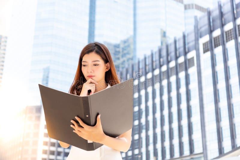 A mulher de negócios bonita encantador olha o documento e o ab de pensamento imagens de stock