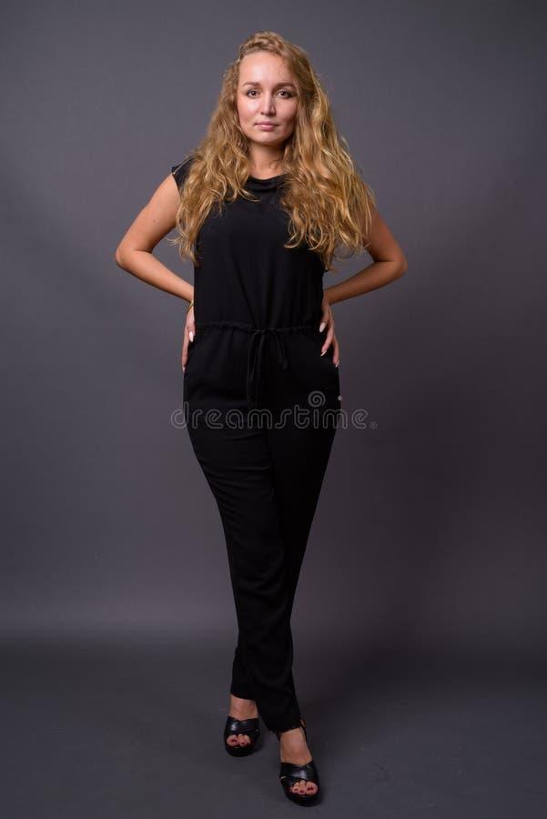 Mulher de negócios bonita nova com cabelo louro ondulado longo contra fotos de stock