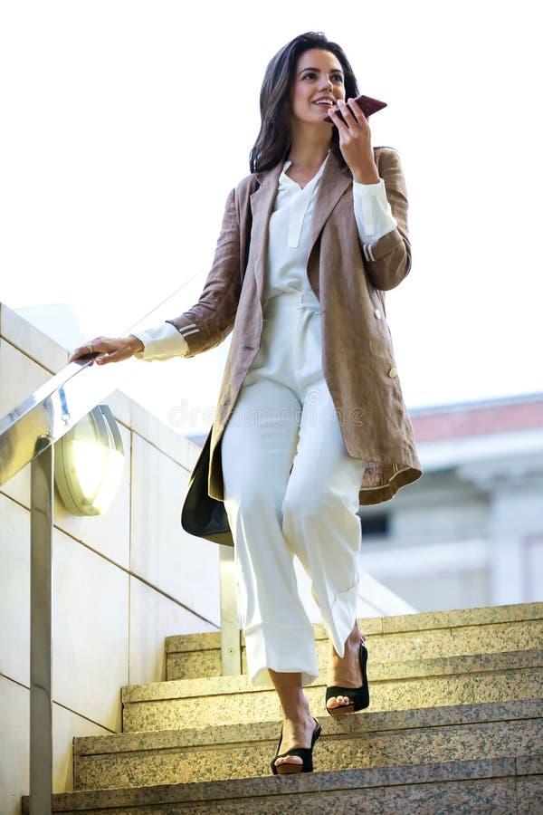 Mulher de negócios bonita nova da forma que fala com seu smartphone na rua fotos de stock