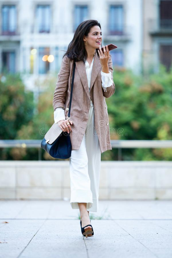 Mulher de negócios bonita nova da forma que fala com seu telefone celular na rua imagem de stock