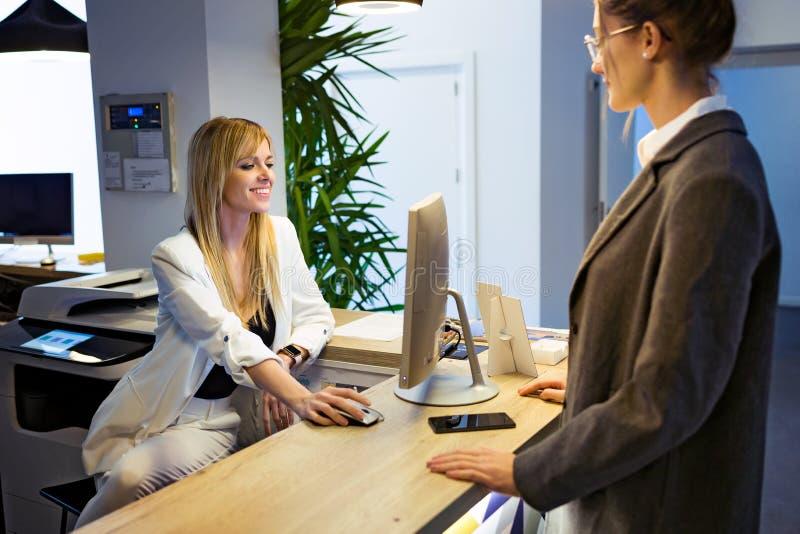 Mulher de negócios bonita nova que faz o registro com o computador na recepção do hotel fotografia de stock