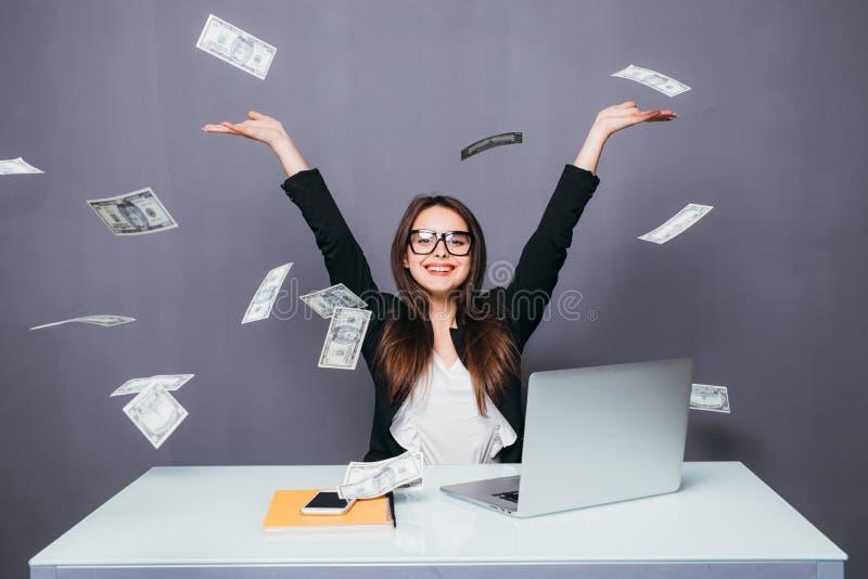 Mulher de negócios bonita nova que joga acima o dinheiro, sentando-se no lugar do escritório com portátil fotografia de stock