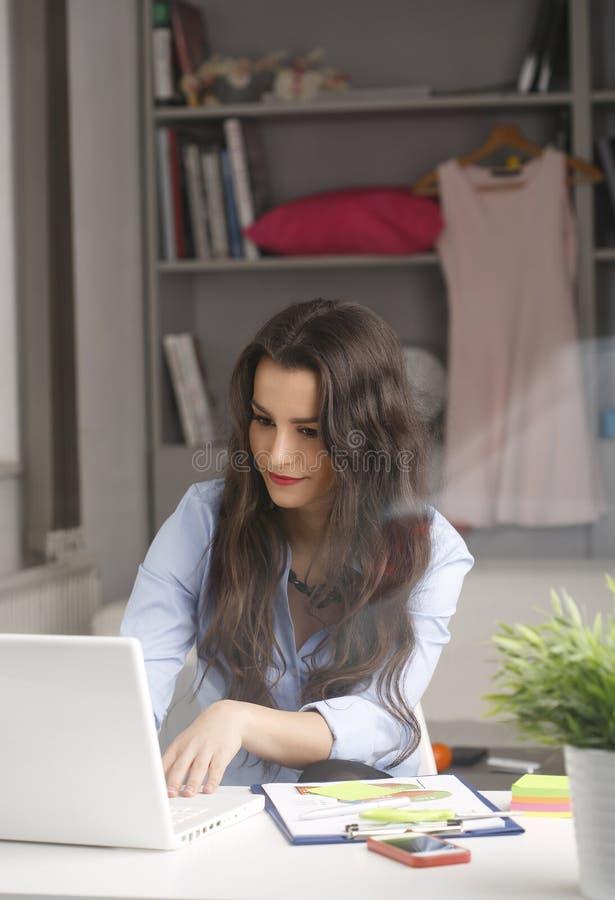 Mulher de negócios bonita nova que trabalha em casa foto de stock