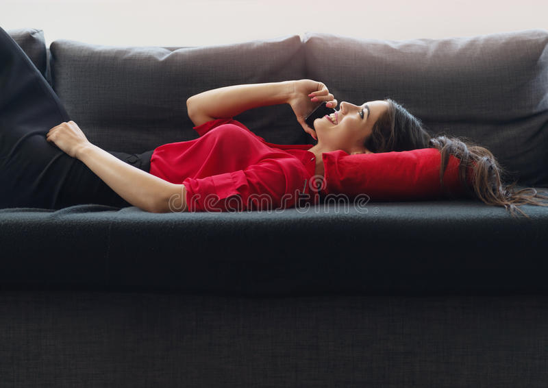 Mulher de negócios bonita, nova que usa um telefone em uma mulher de negócios nova sofaBeautiful que fala sobre o telefone em um  imagens de stock