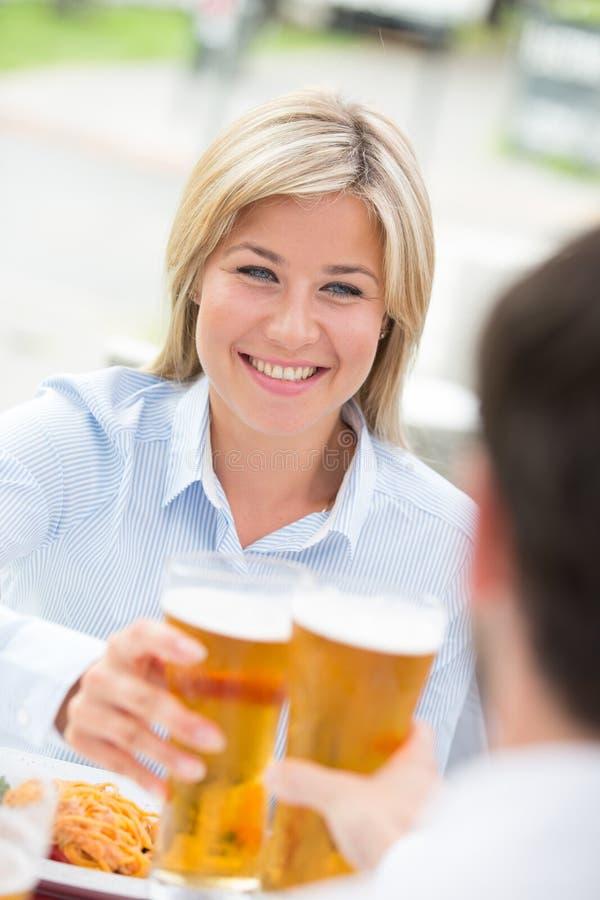 Mulher de negócios bonita que brinda o vidro de cerveja com o colega masculino no restaurante imagens de stock