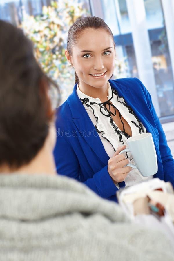 Mulher de negócios bonita que conversa ao colega de trabalho fotos de stock