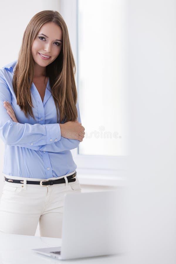 A mulher de negócios bonita que está com braços dobrou-se atrás de um portátil fotografia de stock royalty free