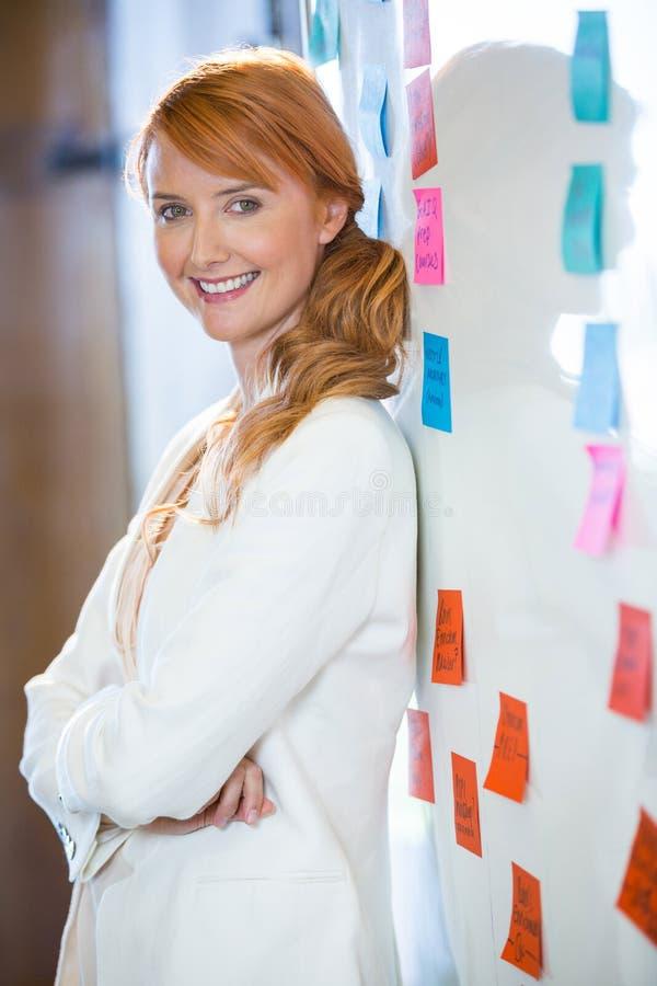 Mulher de negócios bonita que inclina-se no whiteboard fotografia de stock royalty free