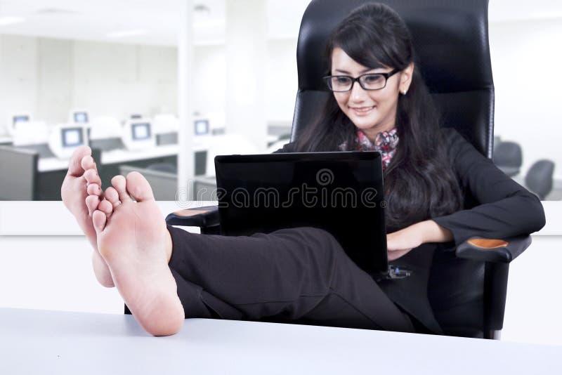 Mulher de negócios bonita que relaxa no escritório foto de stock