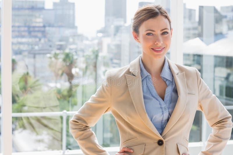 Mulher de negócios bonita que sorri na câmera com mãos nos quadris foto de stock royalty free