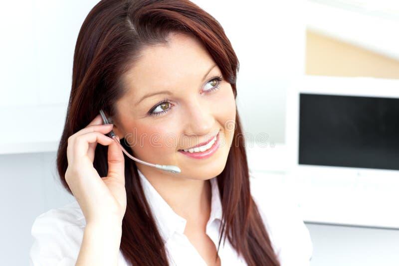 Mulher de negócios bonita que telefona usando auscultadores fotografia de stock