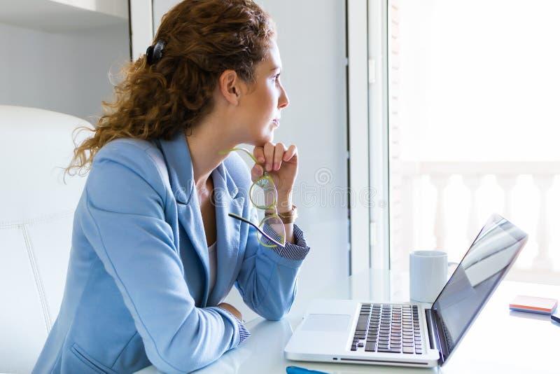 Mulher de negócios bonita que trabalha com seu portátil no escritório imagem de stock
