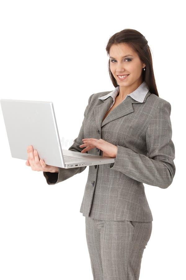 Mulher de negócios bonita que trabalha no portátil foto de stock