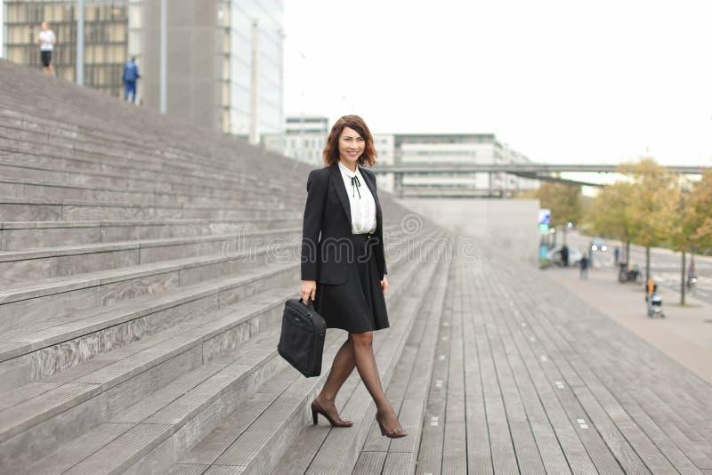 Mulher de negócios bonita que vai para baixo em escadas no fundo alto das construções fotos de stock