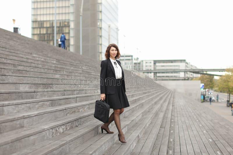 Mulher de negócios bonita que vai para baixo em escadas no fundo alto das construções fotografia de stock