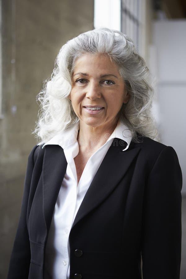 Mulher de negócios branca superior que sorri à câmera, vertical foto de stock
