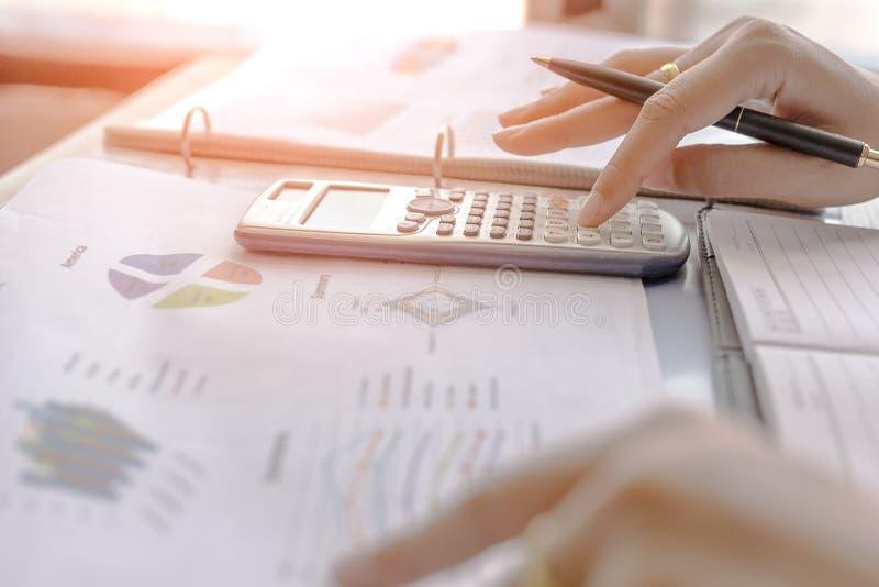 A mulher de negócios calcula sobre o custo e as cartas relatam na tabela, calculadora na mesa do aplanamento financeiro Conceitos imagens de stock royalty free