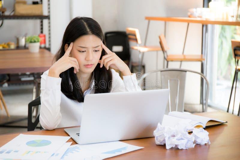 Mulher de negócios cansado e forçada com o sobrecarregado na mesa, asiático da mulher com não ideia preocupada com o portátil da  foto de stock