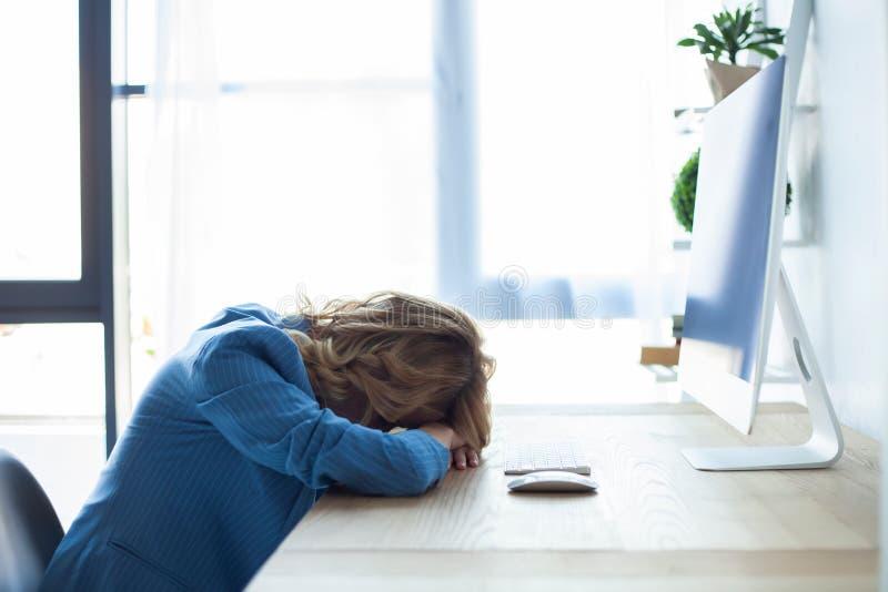 Mulher de negócios cansado que dorme na mesa, na frente do ecrã de computador foto de stock