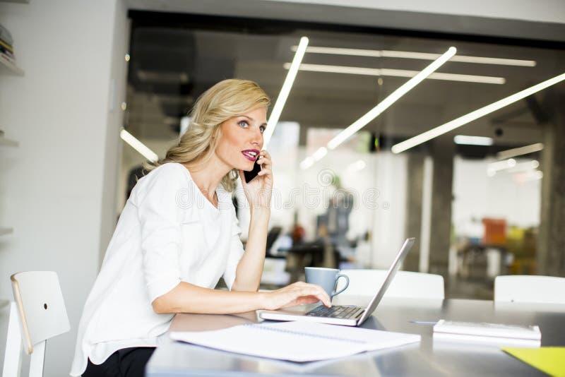 Mulher de negócios caucasiano loura que usa seus telefone celular e sitti fotografia de stock royalty free