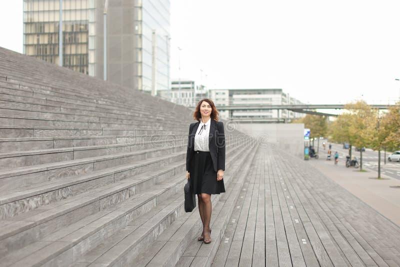 Mulher de negócios caucasiano que está em escadas com saco e em construções altas no fundo foto de stock