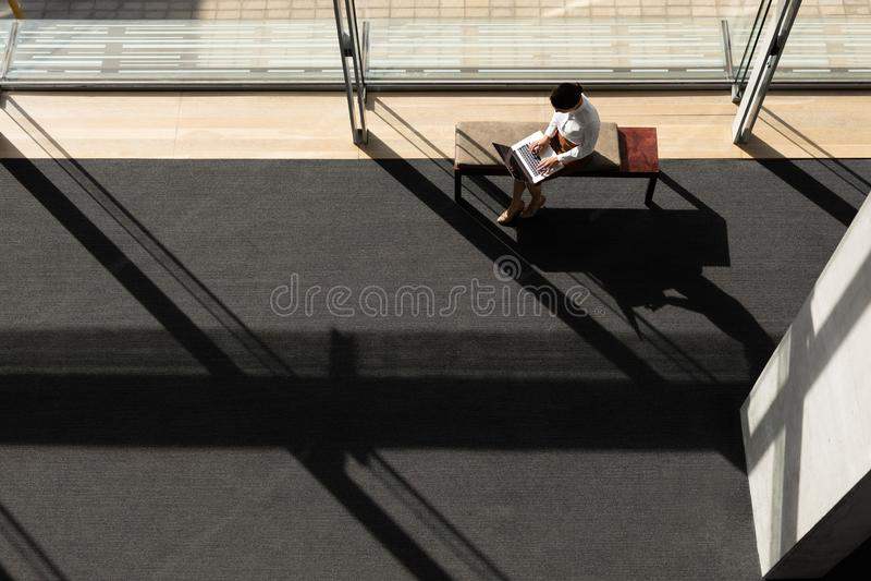 Mulher de negócios caucasiano que senta-se no banco e que trabalha no portátil no escritório imagens de stock royalty free