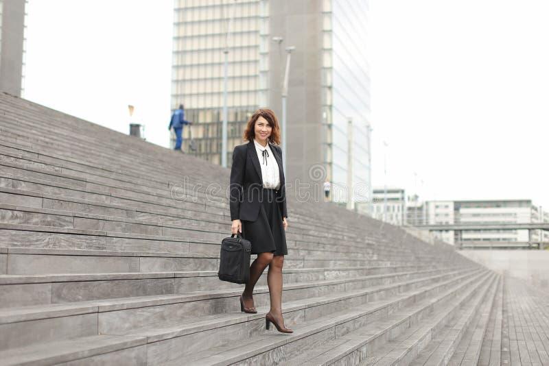 Mulher de negócios caucasiano que vai para baixo em escadas no fundo alto das construções imagem de stock royalty free