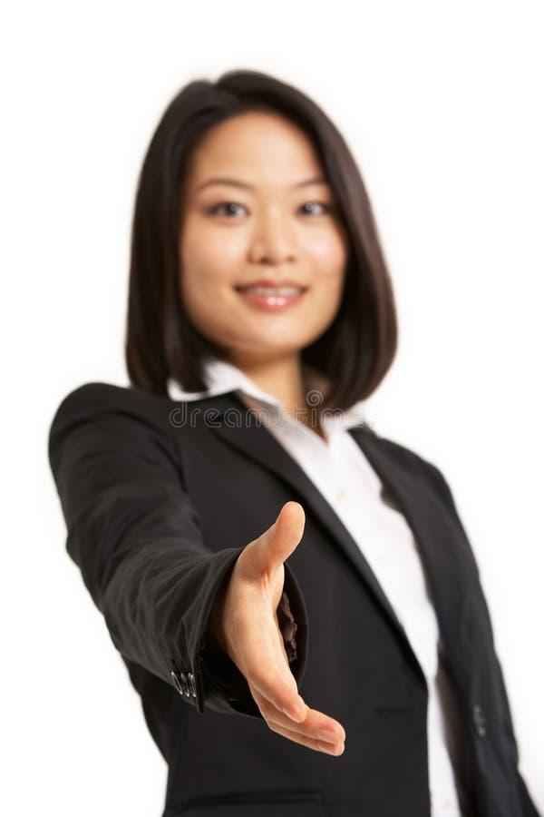 Mulher de negócios chinesa que alcanga para fora para agitar H fotos de stock